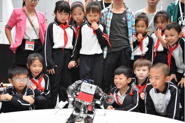 2018年10月,在第二十届中国机器人及人工智能大赛上,小观众被进行击剑比赛的仿人机器人吸引。新华社图